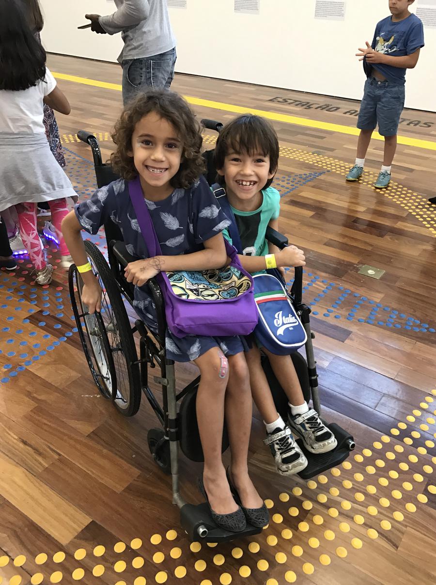 Tarsila e Lorenzo brincando com uma cadeira de rodas em uma exposição lúdica na Biblioteca Parque do centro do Rio | © Lima Andruška