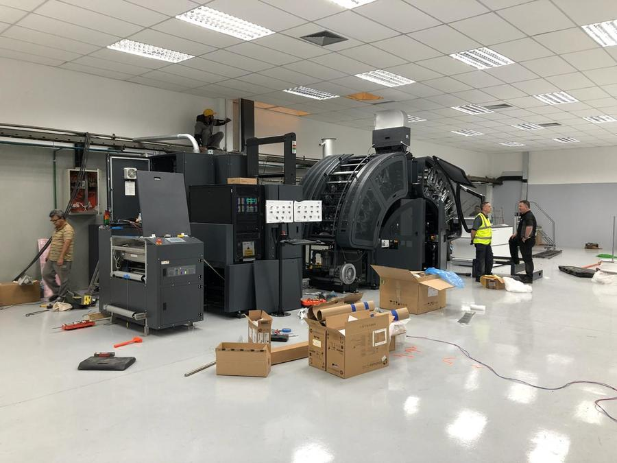 Work in progress: equipe instala novo equipamento com o qual a gráfica espera dobrar sua capacidade de produção | © Divulgação