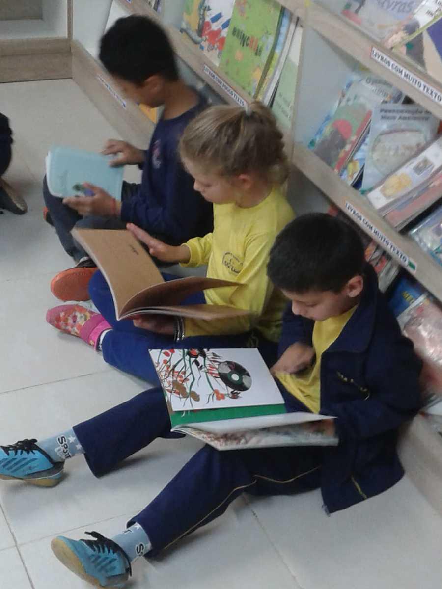 Crianças lendo na Biblioteca da Escola Municipal de Ensino Fundamental Santa Lúcia (Caxias do Sul - RS)