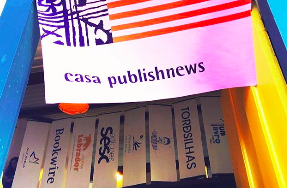 Flâmula na frente da Casa PublishNews e os banners de seus parceiros ao fundo   © Mariana Bueno