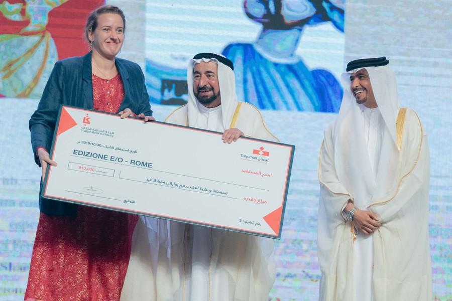 Representante da editora italiana Edizione E/O recebe o cheque simbólico pelo prêmio de tradução da feira | Divulgação