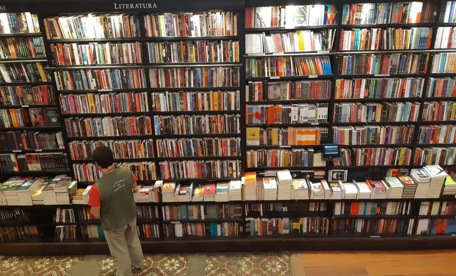 Livreiro organiza estante na Livraria da Travessa de Botafogo | © Leonardo Neto